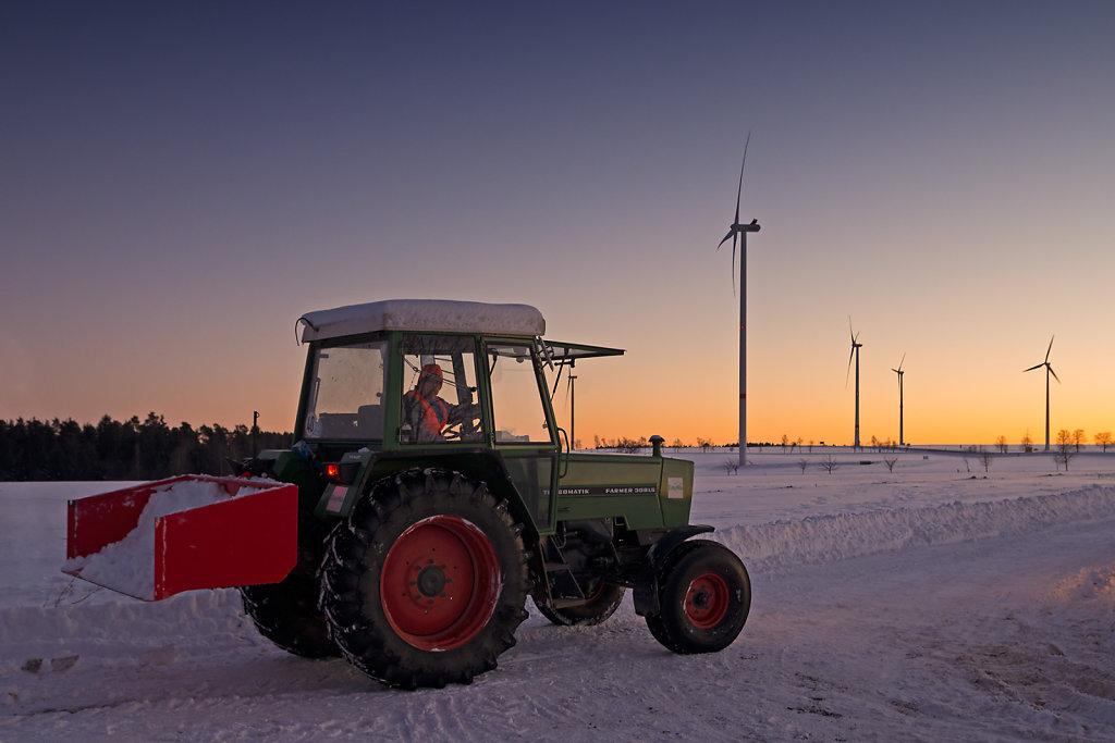 Traktor vor Windrädern